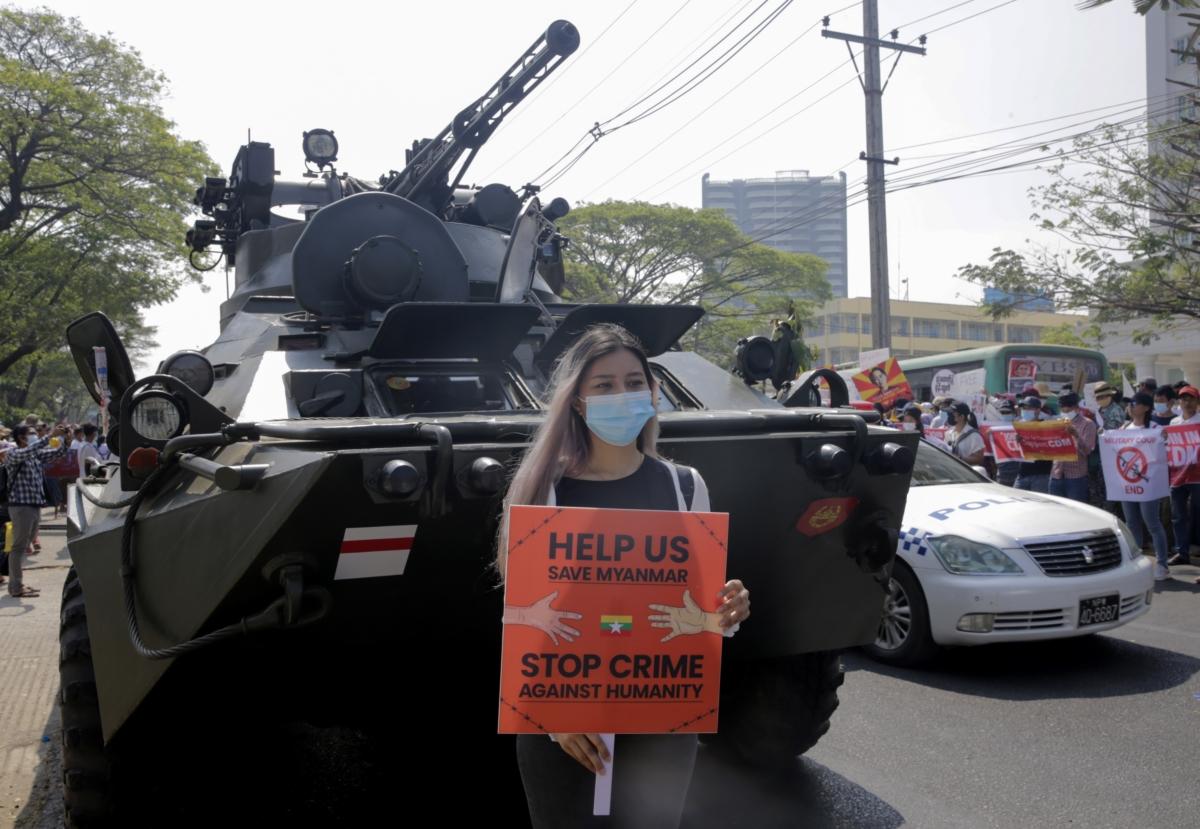 미얀마 최대 도시 양곤에서 쿠데타 항의 시위에 참여한 한 여성이 장갑차 앞에서 '우리를 도와 미얀마를 지켜달라, 인권억압 범죄를 멈추라'고 적힌 팻말을 들고 있다.